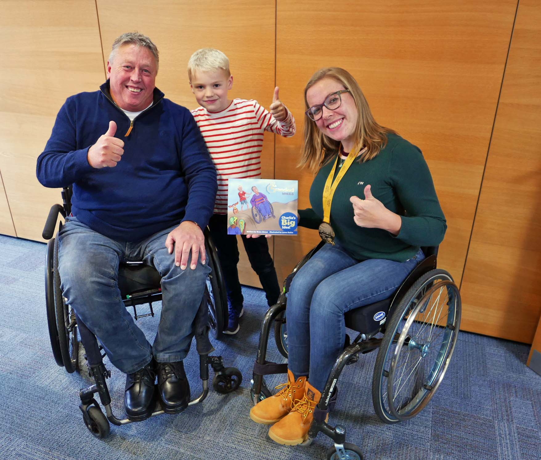 "Brian, Charles and Hannah Cockroft MBE pose for a photo with the first book of ""The Adventures of Grandad Wheels"" series."